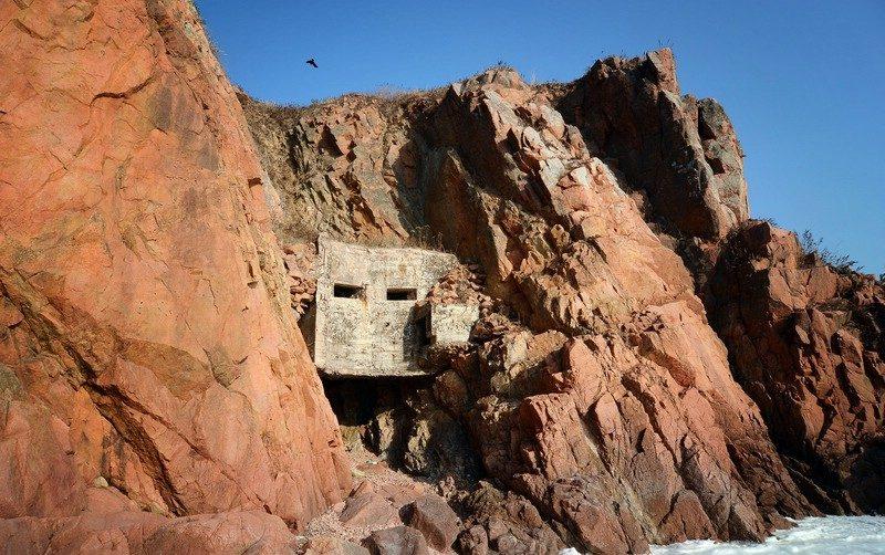 Четырёхамбразурный ДОТ №10 «Скала» на острове Русский был построен в 1934 году. Расположен на западном побережья б. Холуай. Класс защиты - М-2.