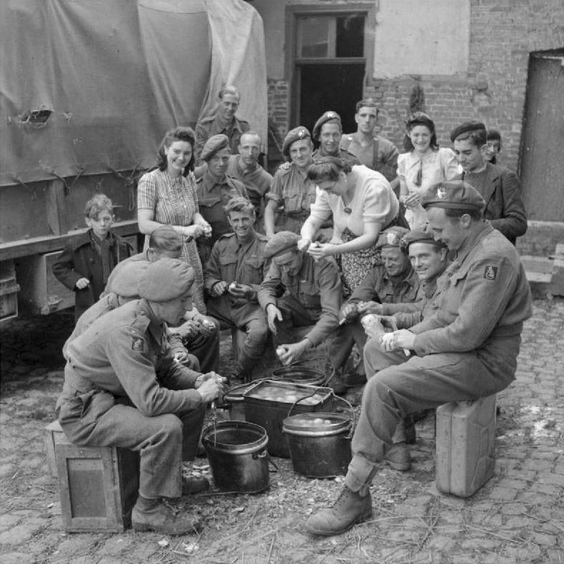 Французские женщины помогают британцам чистить картошку возле Сен-Поль. 3 сентября 1944 г.