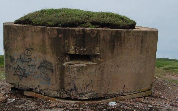 Трёхамбразурный бетонный ДОТ №216 на острове Попова был построен в 1941 году. Расположен в средней части побережья бухты Пограничная. Класс-защиты М-3.