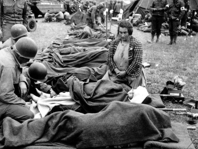 Американский полевой госпиталь. Местная жительница у носилок своего раненого ребенка. 1944 г.