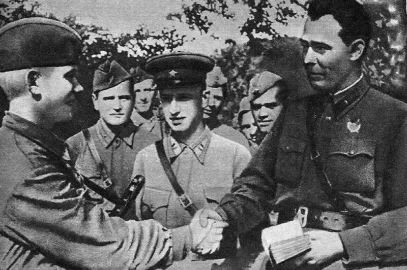 Бригадный комиссар Л. И. Брежнев вручает партийный билет помкомвзвода А. Малому, 1942 г.