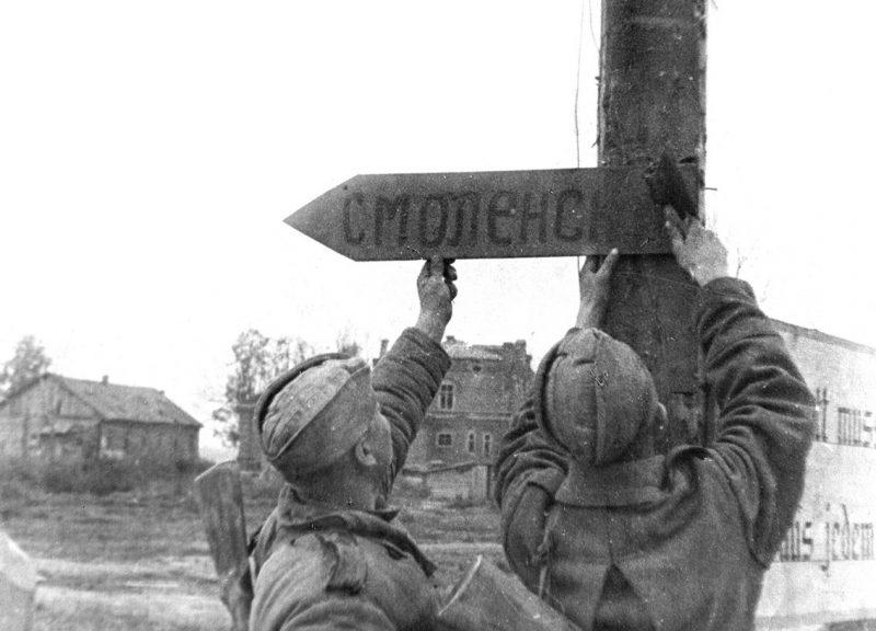 На одной из улиц освобождённой Духовщины бойцы прибивают указатель с надписью «Смоленск».
