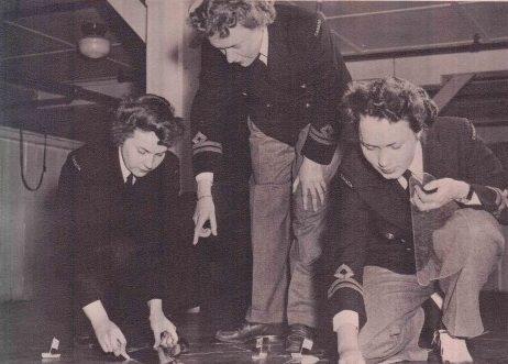 Лейтенант Кэрол Хендри и ее подчиненные из WRCNS строят макет позиции на тактическом столе. 1944 г.