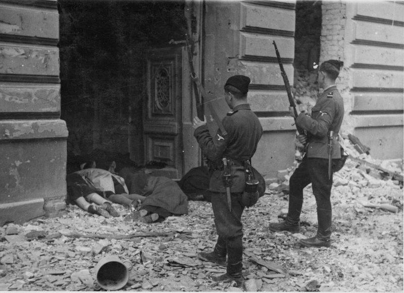 Двое «хиви» над телами убитых евреев Варшавского гетто. Май 1943 г.