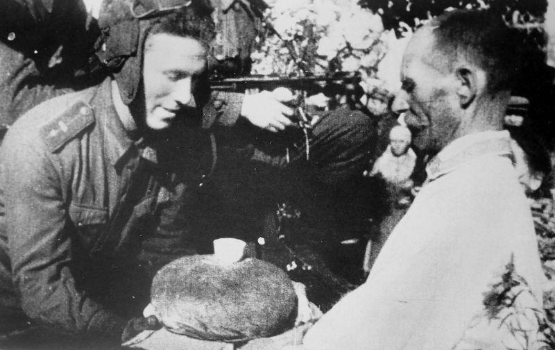 Житель освобожденного Глухова вручает танкисту хлеб с солью. 30 августа 1943 г.
