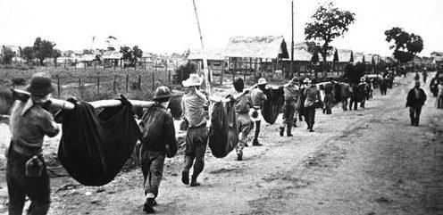 Американские военнопленные на подручных носилках несут своих товарищей во время «Марша смерти» в Батаане. Филиппины, май 1942 г.