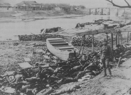 Офицер японской армии стоит возле тел китайцев, убитых японскими военными в Нанкине. Декабрь 1937 г.