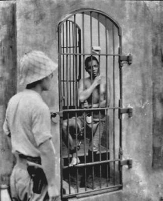 Солдат японской армии, охраняющий пленного филиппинца. Манила, 1942 г.