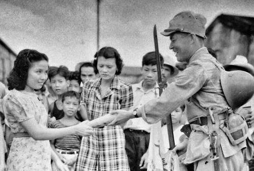Пропагандистская фотография японского солдата, которого приветствуют филиппинцы. Манила, 1942 г.