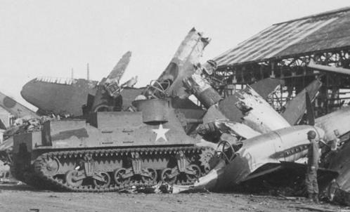 Американская САУ M7 «Priest» крушит японские авиационные фюзеляжи на заводе в Гифу. 1945 г.