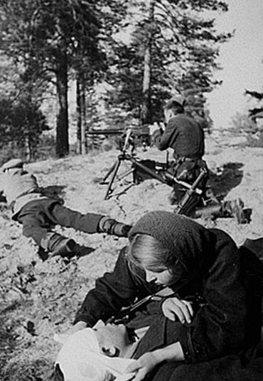 Санитарка партизанского отряда перевязывает раненного. Белоруссия, декабрь 1943 г.