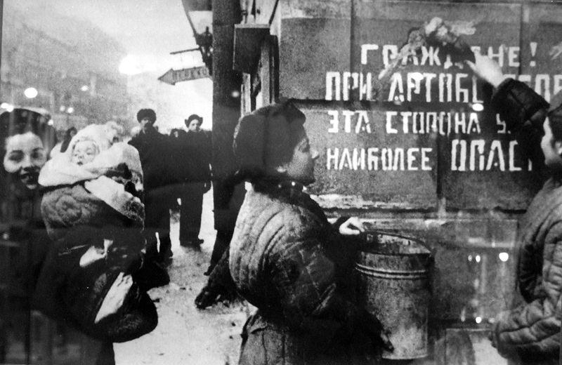 Ленинградцы закрашивают надпись «Граждане! При артобстреле эта сторона улицы наиболее опасна», январь 1944 года.