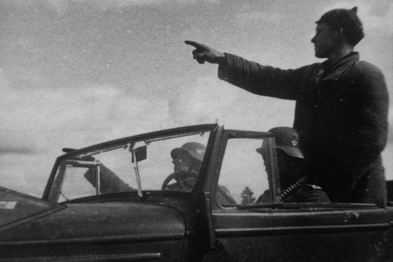 Коллаборационист показывает полевым жандармам место расположения советских партизан. Пропагандистское фото.1941 г.