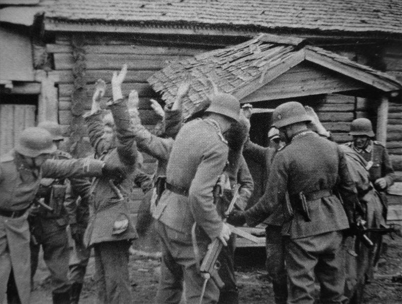 Полевые жандармы обыскивают партизан. Пропагандистское фото.1941 г.