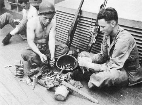 Морские пехотинцы снаряжают магазины и чистят оружие по пути в Тараву на борту транспорта Зейлин. Октябрь 1943 г.