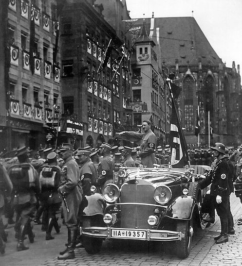 Адольф Гитлер приветствует штурмовиков СА. Позади Гитлера стоит Якоб Гриммингер со Знаменем крови. 1935 г.