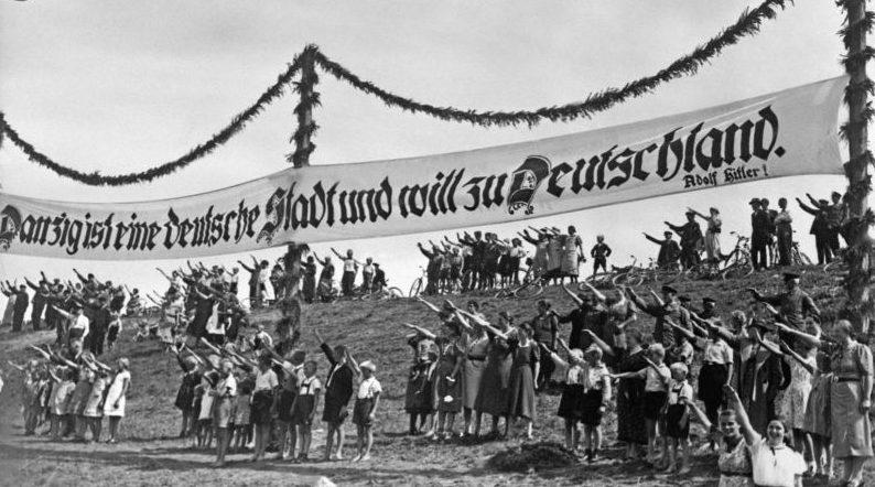 Немецкие жители Данцига на демонстрации за присоединение города к Германии. Надпись на транспаранте: «Данциг - немецкий город и хочет в Германию. Адольф Гитлер!». Август 1939 г.