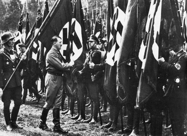 Адольф Гитлер с Якобом Гриммингером «освячивает» Знаменем крови нацистские стандарты на собрании партии. Нюрнберг. 1933 г.