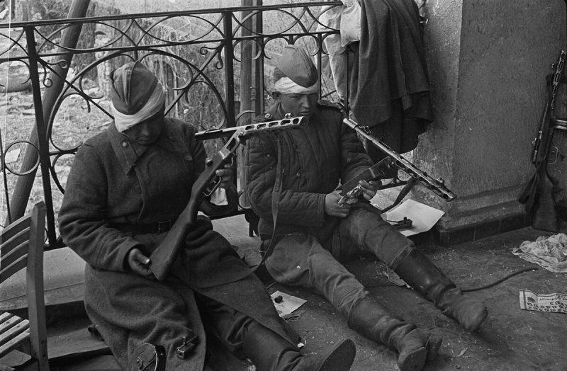 Раненые красноармейцы чистят свое оружие после боев за Берлин.