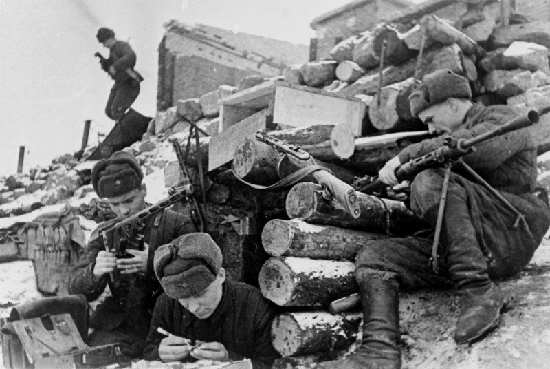 Красноармейцы у землянки в Сталинграде за чисткой оружия.