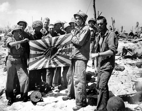 Морские пехотинцы с захваченным японским флагом на острове Энгеби. Февраль 1944 г.