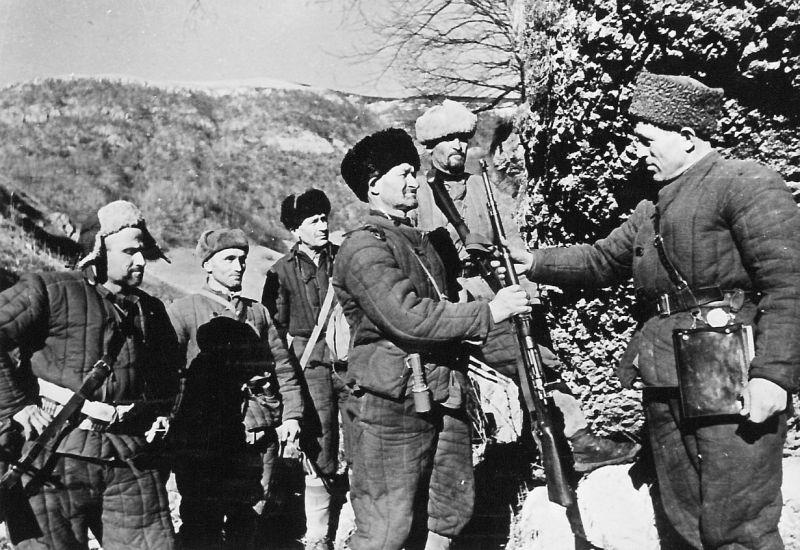Командир партизанского отряда Орджоникидзевского района Северо-Осетинской АССР Дзарахмет Мулухов вручает бойцу трофейный немецкий карабин. 24 декабря 1942 г.
