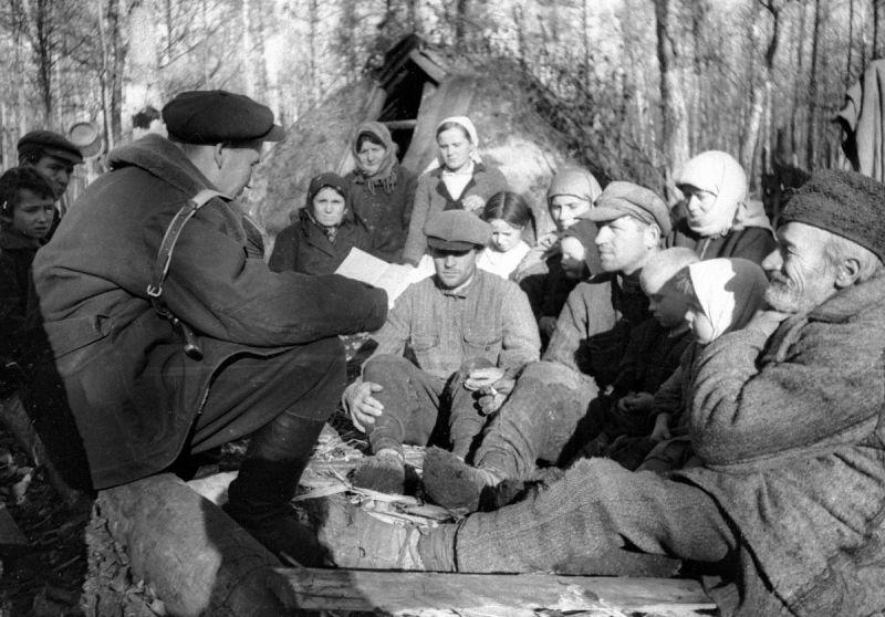 Партизаны в лесном лагере слушают сводку Совинформбюро. 1942 г.