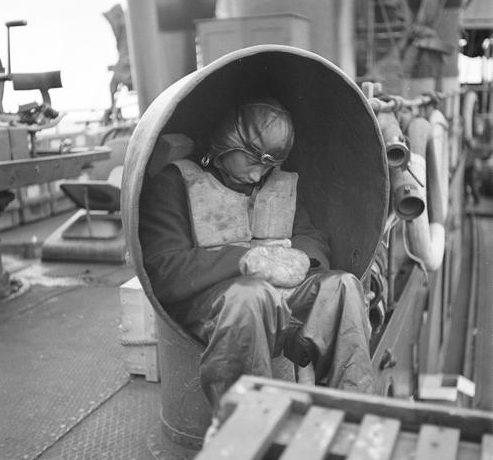 Уставший моряк на канонерской лодке после битвы на острове Сомери. 10 июля 1942 г.
