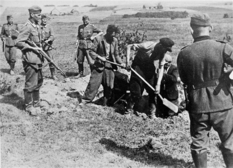 Партизаны роют себе могилу под охраной немецких солдат. 1942 г.