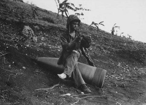 Морской пехотинец на неразорвавшимся 406-мм снаряде американского линкора, обеспечивавшего огневую поддержку на Сайпане. Июль 1944 г.