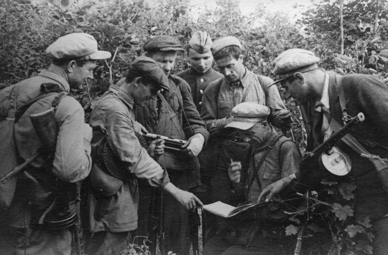 Партизаны изучают немецкие документы. Орловская область, 1942 г.