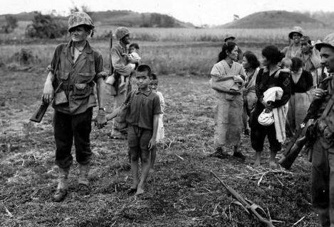 Морские пехотинцы уводят женщин и детей в более безопасное место. Сайпан, июль 1944 г.