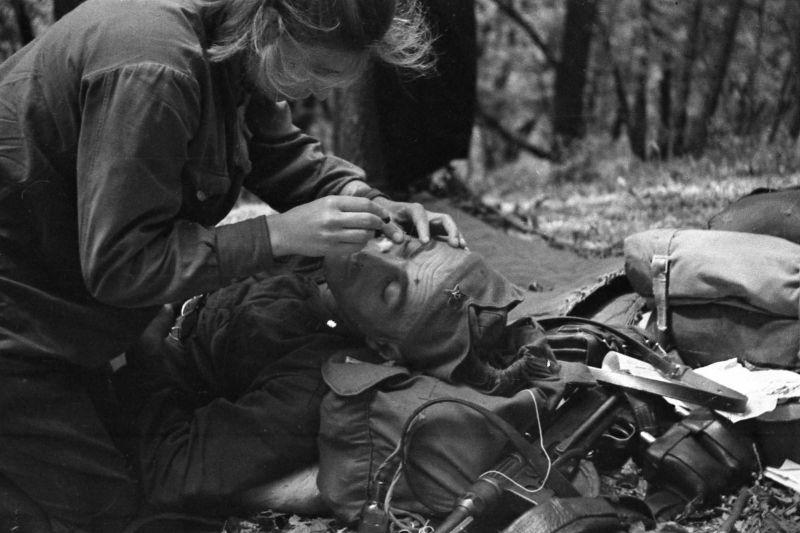 Разведчик специальной разведгруппы «Соколы» оказывает помощь партизану. Август 1943 г.