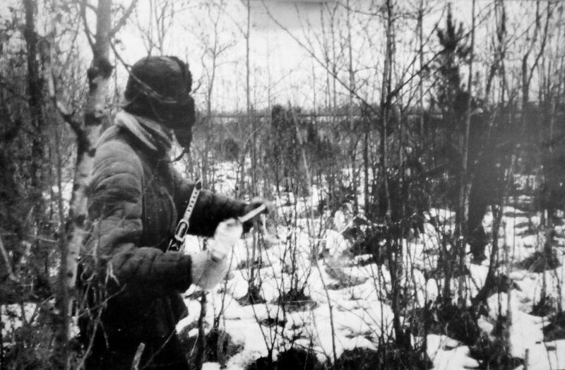 Партизан 5-й Ленинградской партизанской бригады готовится готовиться подорвать эшелон противника. Декабрь 1943 г.