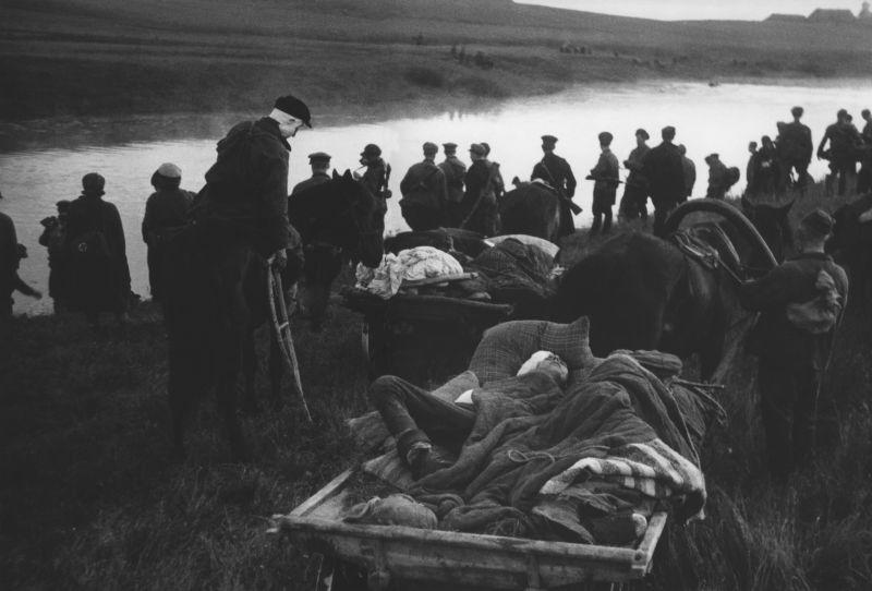 Советские партизаны переправляют раненых через реку. 1943 г.