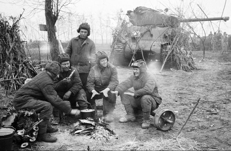 Танкисты 1-го Прибалтийского фронта отдыхают у костра возле у танка М4 «Шерман». Октябрь 1944 г.