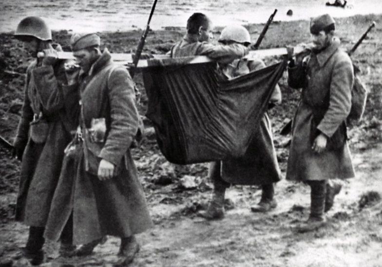 Красноармейцы выносят раненного на берегу Волхова. 1943 г.