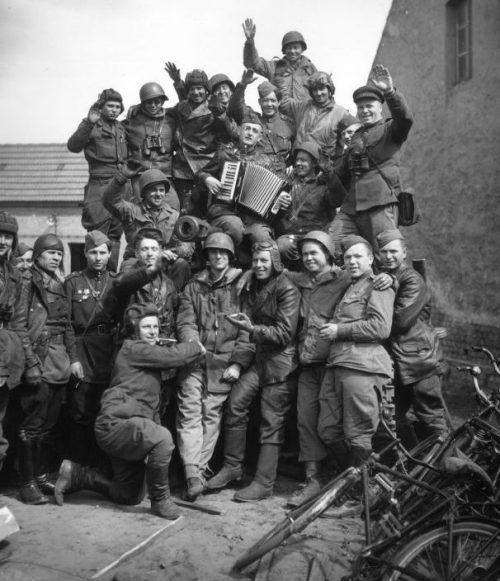 Советские танкисты-самоходчики и американские военные у САУ СУ-76 в немецком городе Грибо. Май 1945 г.