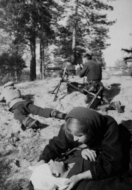 Санитарка отряда имени Котовского Александра Дордюк перевязывает раненого партизана во время боя в Белоруссии. 1943 г.