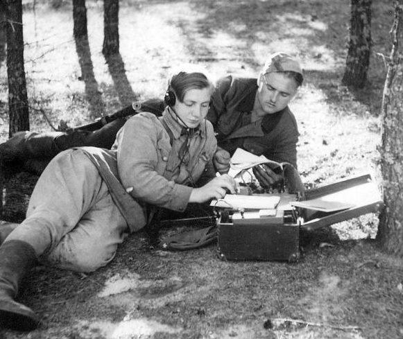 Радисты партизанской бригады «Смерть фашизму» Вячеслав Бондарь и Леонид Колисниченко передают радиограмму. Июнь 1944 г.