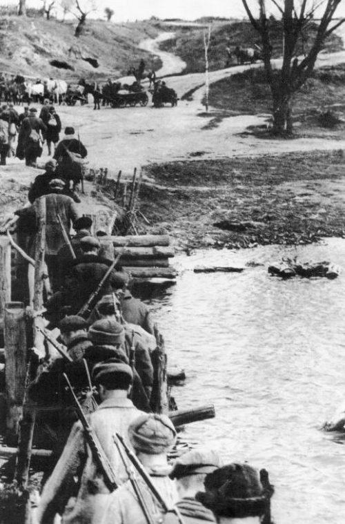Советские партизаны переходят реку по мосту. 1944 г.