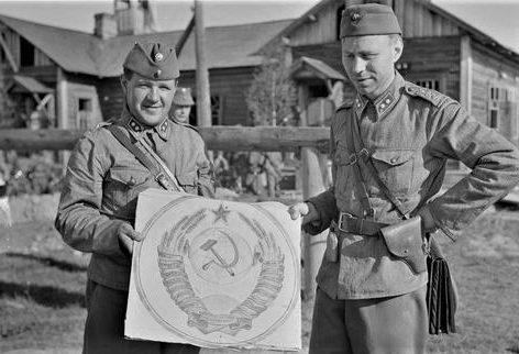 Офицеры финской армии позируют с гербом СССР на захваченном советском пограничном посту в деревне Вазонваара Вена. 1941 г.