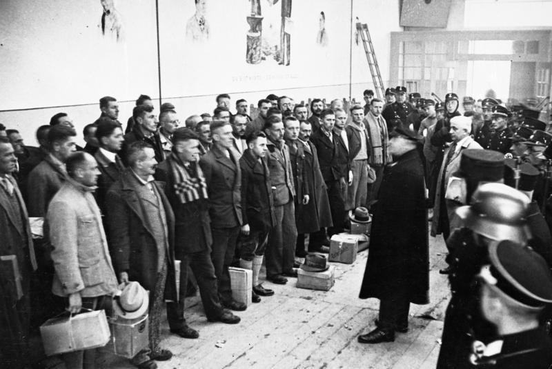 Комендант лагеря произносит речь перед заключенными, которых выпускают в рамках акции помилования перед Рождеством 1933 года.
