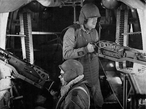 Пулеметчики в шлемах М-3 в салоне бомбардировщика В-17.
