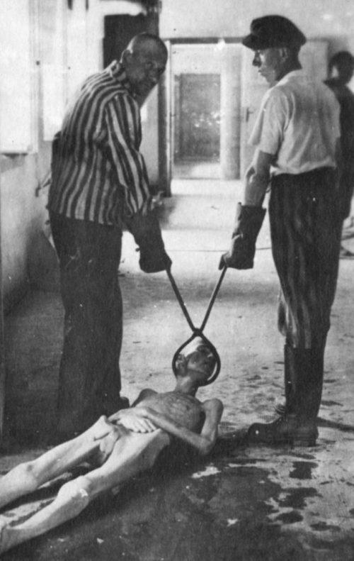 Заключенные демонстрируют процесс уничтожения трупов в крематории концлагеря Дахау.