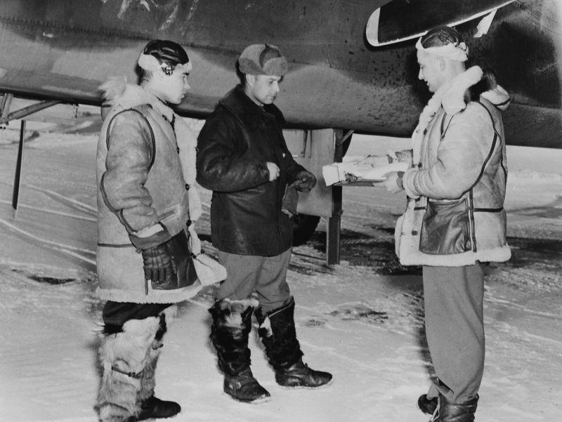 Советские пилоты Сусин и Карпов с сержантом ВВС США Алексом Хомончуком на аэродроме Лэдд Филд на Аляске. 1943 г.