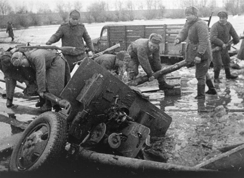 Артиллеристы вытягивают провалившуюся 76,2-мм дивизионную пушку ЗиС-3. Бранденбург, февраль 1945 г.