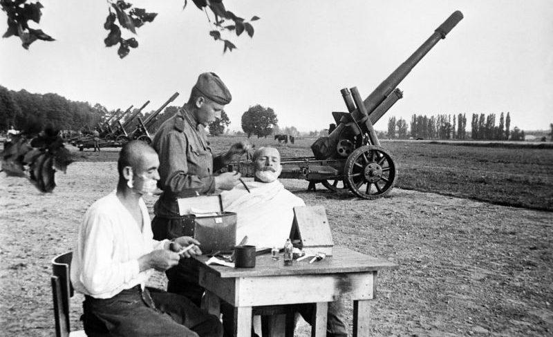 Артиллеристы бреются возле 152-мм гаубиц-пушек МЛ-20 под Веной. Первые мирные дни. Май 1945 г.
