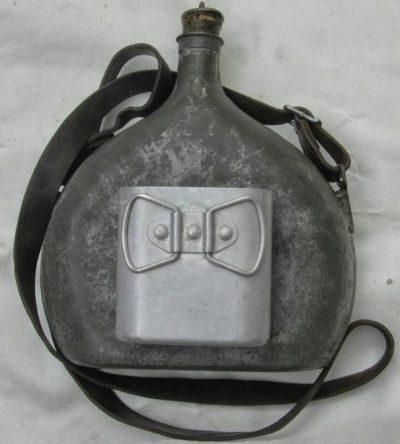 Армейская фляга образца 1935 года с кружкой и в суконном чехле. Размеры: высота – 24см, ширина 21 см, толщина – 8 см.