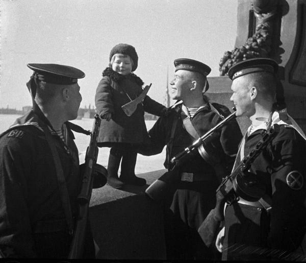 Моряки Балтийского флота с маленькой девочкой Люсей, родители которой умерли в блокаду. Ленинград, май 1943 г.